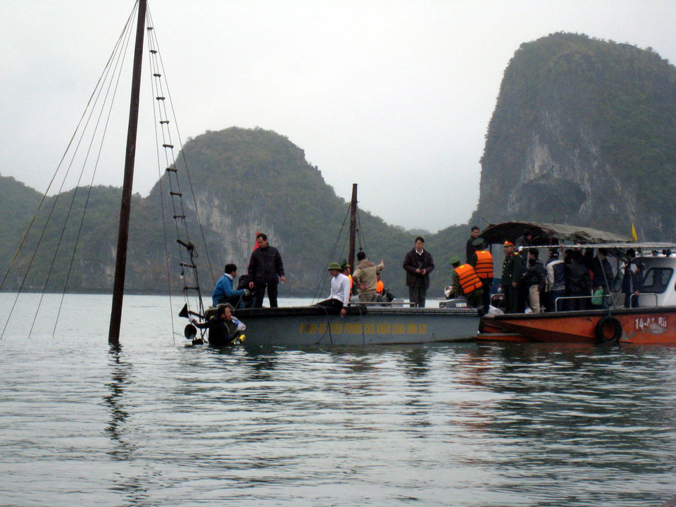 FILE - In this Feb. 17, 2012 file photo, Vietnamese rescuers search for victims of a sunken tourist boat of which sail pole sticks out from the water on Halong Bay in northern Quang Ninh province, Vietnam. A total of 12 people from nine nations died when their boat sank early in the morning. Each day, up to 10,000 tourists from around the world sail around the bay, a UNESCO-heritage site and one of the country's most visited tourist attractions, and gaze at its stunning limestone pillars and caves. But at least four deadly accidents over the last 10 years and many more alarming safety incidents recounted on traveler's blogs have led to allegations that the ships are cutting corners. (AP Photo/VNA, Dinh Manh Tu, File)