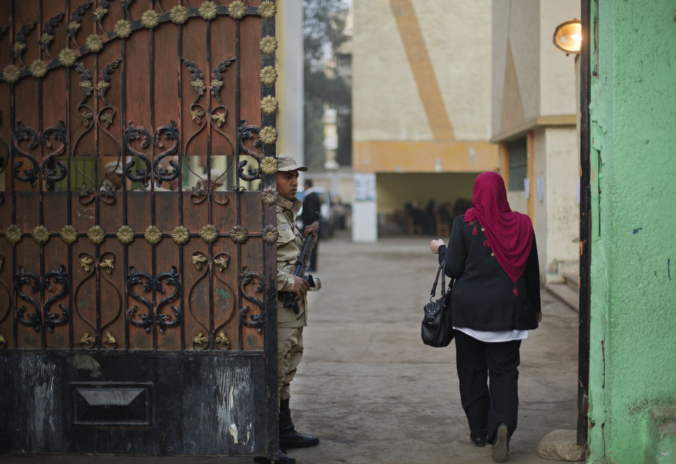 Photo - An Egyptian army soldier stand guards the entrance of a polling  station as a woman walks in to cast her vote in the country's constitutional referendum in Cairo, Egypt, Tuesday, Jan. 14, 2014. Egyptians have started voting on a draft for their country's new constitution that represents a key milestone in a military-backed roadmap put in place after President Mohammed Morsi was overthrown in a popularly backed coup last July. (AP Photo/Khalil Hamra)