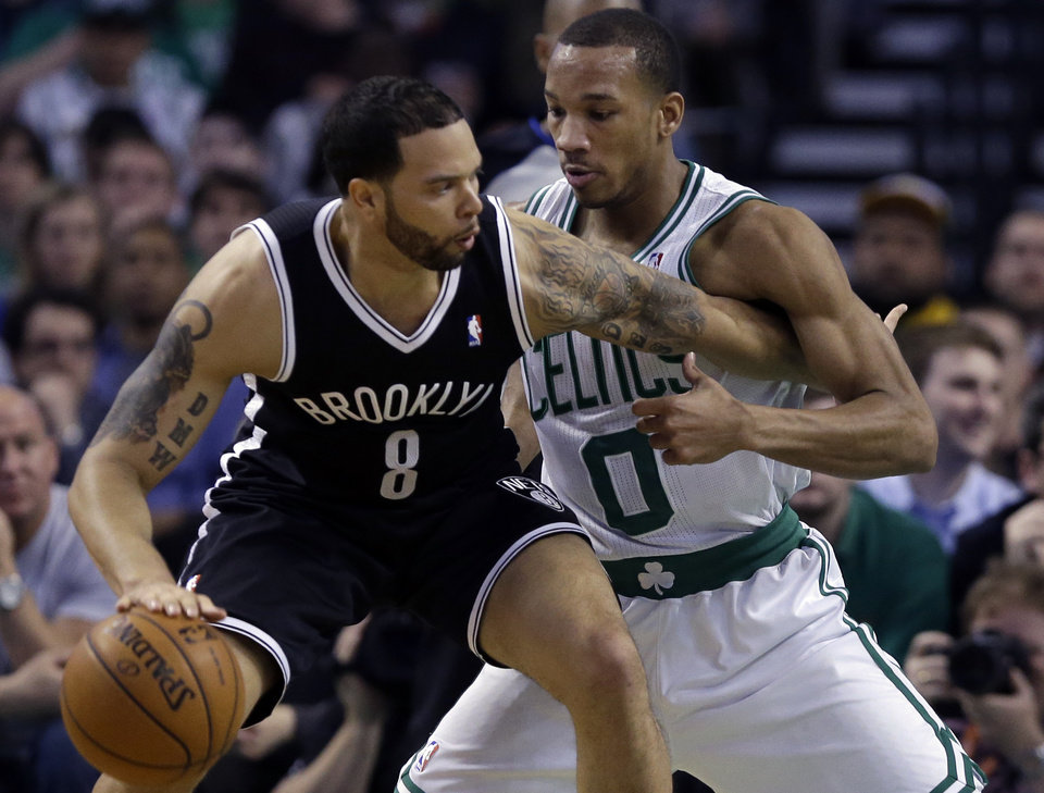 Photo - Brooklyn Nets point guard Deron Williams (8) tries to drive against Boston Celtics point guard Avery Bradley (0) during the second quarter of an NBA basketball game in Boston, Wednesday, April 10, 2013. (AP Photo/Elise Amendola)