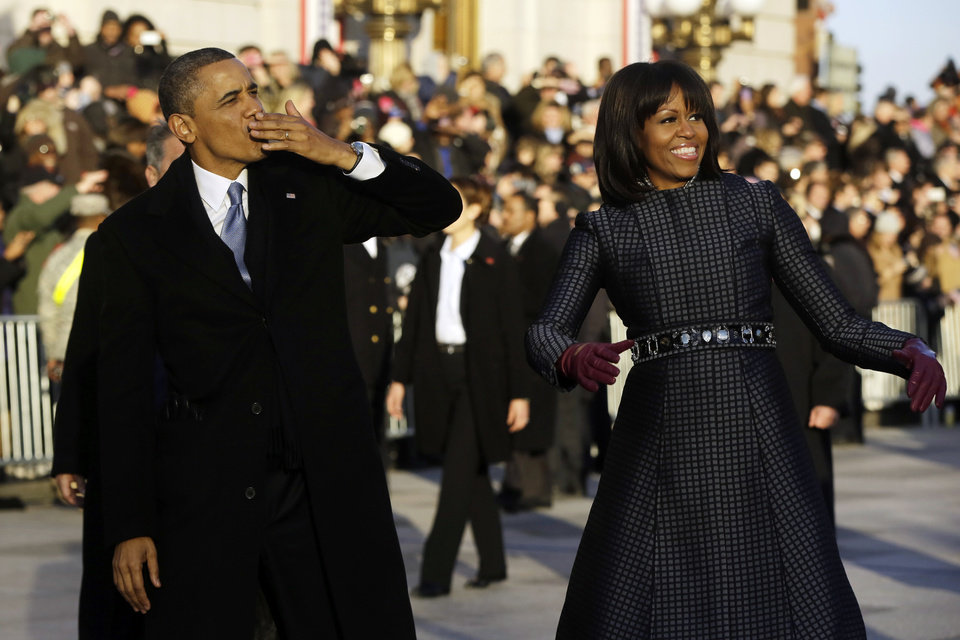 President Barack Obama blows a kiss as he and first lady Michelle Obama walk on Pennsylvania Avenue near the White House in the Inauguration Parade during the 57th Presidential Inauguration in Washington, Monday, Jan. 21, 2013. (AP Photo/Charles Dharapak) ORG XMIT: WHCD102