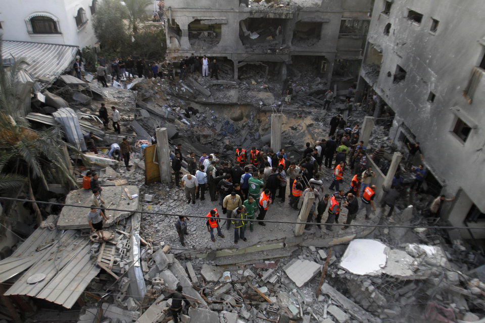 Photo -   Palestinians stand in the rubble of the Daloo family house following an Israeli air strike in Gaza City, Sunday, Nov. 18, 2012. Palestinian medical officials say at least 10 civilians, including women and young children, have been killed in an Israeli airstrike in Gaza City. (AP Photo/Hatem Moussa)