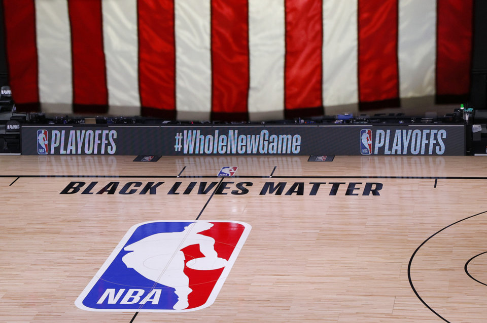 Photo - An empty court and bench are shown following the scheduled start time of Game 5 of an NBA basketball first-round playoff series, Wednesday, Aug. 26, 2020, in Lake Buena Vista, Fla. All three NBA playoff games scheduled for Wednesday were postponed, with players around the league choosing to boycott in their strongest statement yet against racial injustice.  (Kevin C. Cox/Pool Photo via AP)