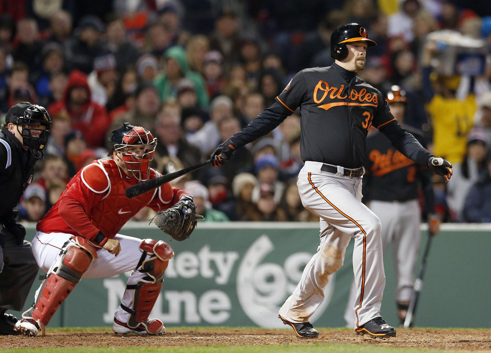Photo - Baltimore Orioles' Matt Wieters follows through on an RBI single in front of Boston Red Sox's A.J. Pierzynski in the fifth inning of a baseball game in Boston, Friday, April 18, 2014. (AP Photo/Michael Dwyer)