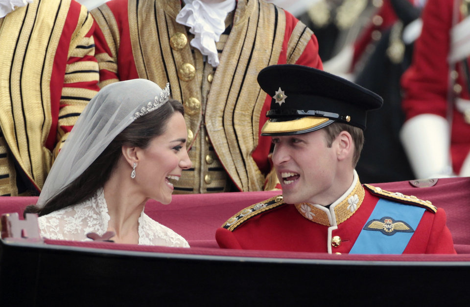 Photo - Britain's Prince William, right, and his wife Kate, the Duchess of Cambridge, left, make the journey by carriage procession to Buckingham Palace past crowds of spectators following their marriage at Westminster Abbey, London, Friday, April 29, 2011. (AP Photo/Matt Cardy, Pool) ORG XMIT: RWDA114
