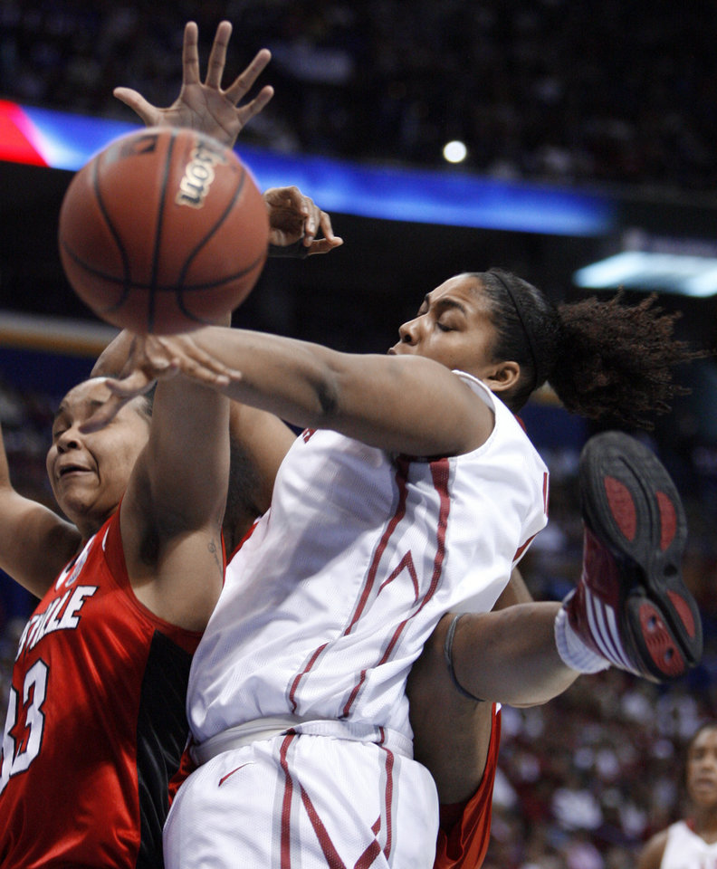 Photo - Abi Olajuwon (right) and Monique Reid fight for a rebound in the first half as the University of Oklahoma plays Louisville at the 2009 NCAA women's basketball tournament Final Four in the Scottrade Center in Saint Louis, Missouri on Sunday, April 5, 2009. 