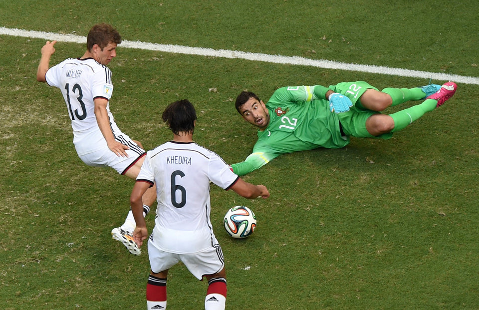 Photo - Germany's Thomas Mueller, left, scores his side's 4th goal during the group G World Cup soccer match between Germany and Portugal at the Arena Fonte Nova in Salvador, Brazil, Monday, June 16, 2014.  (AP Photo/Francois Marit, pool)