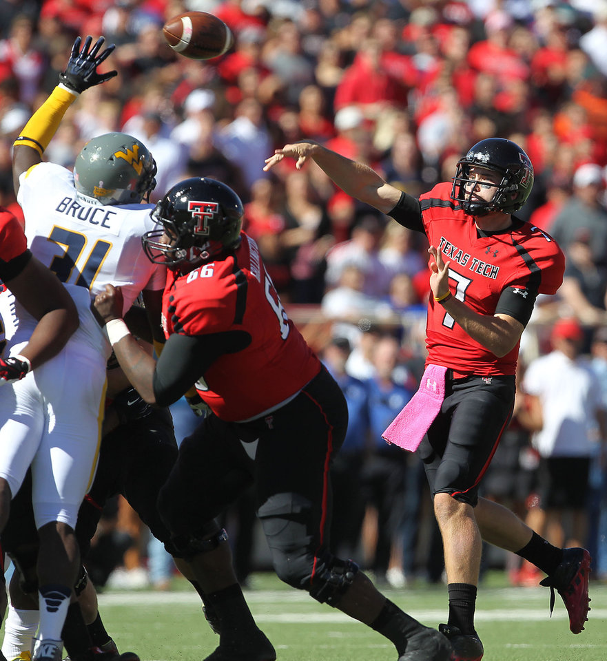 Photo -   Texas Tech's Seth Doege throws over West Virginia's Isaiah Bruce while getting a block from Deveric Gallington (66) during their NCAA college football game in Lubbock, Texas, Saturday, Oct. 13, 2012. (AP Photo/Lubbock Avalanche-Journal, Stephen Spillman)