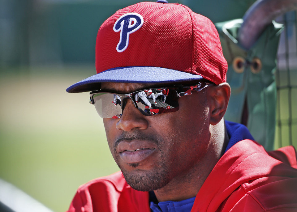 Photo - Philadelphia Phillies Jimmy Rollins sits in the dugout after not playing for the third consecutive game during a spring exhibition baseball game against the New York Yankees in Clearwater, Fla., Thursday, March 13, 2014.  Rollins said the situation was unusual; that he is healthy, therefore he is not sure why Phillies manager Ryne Sandberg is not playing him. (AP Photo/Kathy Willens)