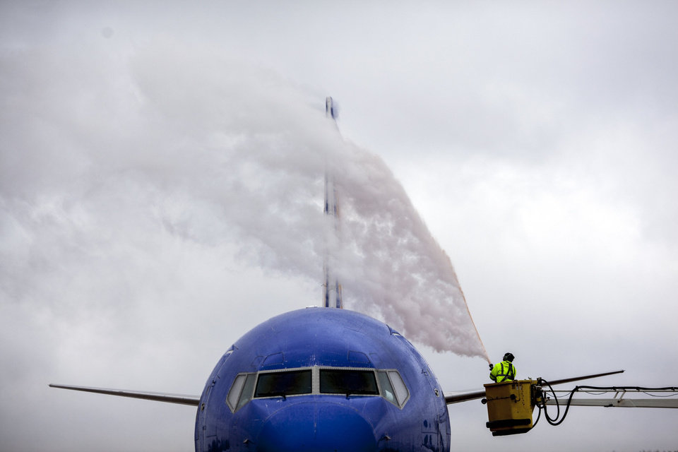 Photo - A worker from Wilson Air Center de-ices a Southwest Airlines plane before it lifts off to Orlando, Fla., Friday, Dec. 6, 2013, at the Memphis International Airport in Memphis, Tenn. The National Weather Service said winter storm warnings and watches and an ice storm warning were in effect for northern Mississippi and West Tennessee on Friday. (AP Photo/The Commercial Appeal, Mark Weber)