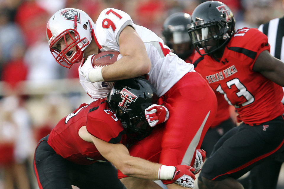 New Mexico\'s Lucas Reed is tackled by Texas Tech\'s Blake Dees (25) and Sam Eguavoen (13) during their NCAA college football game in Lubbock, Texas, Saturday, Sept. 15, 2012. (AP Photo/The Avalanche-Journal, Stephen Spillman) ALL LOCAL TV OUT ORG XMIT: TXLUB102