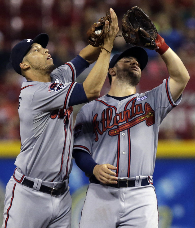 Photo - Atlanta Braves shortstop Andrelton Simmons, left, avoids a collision with second baseman Tommy La Stella as he catches a pop fly hit by Cincinnati Reds' Brayan Pena in the fourth inning of a baseball game, Saturday, Aug. 23, 2014, in Cincinnati. (AP Photo/Al Behrman)