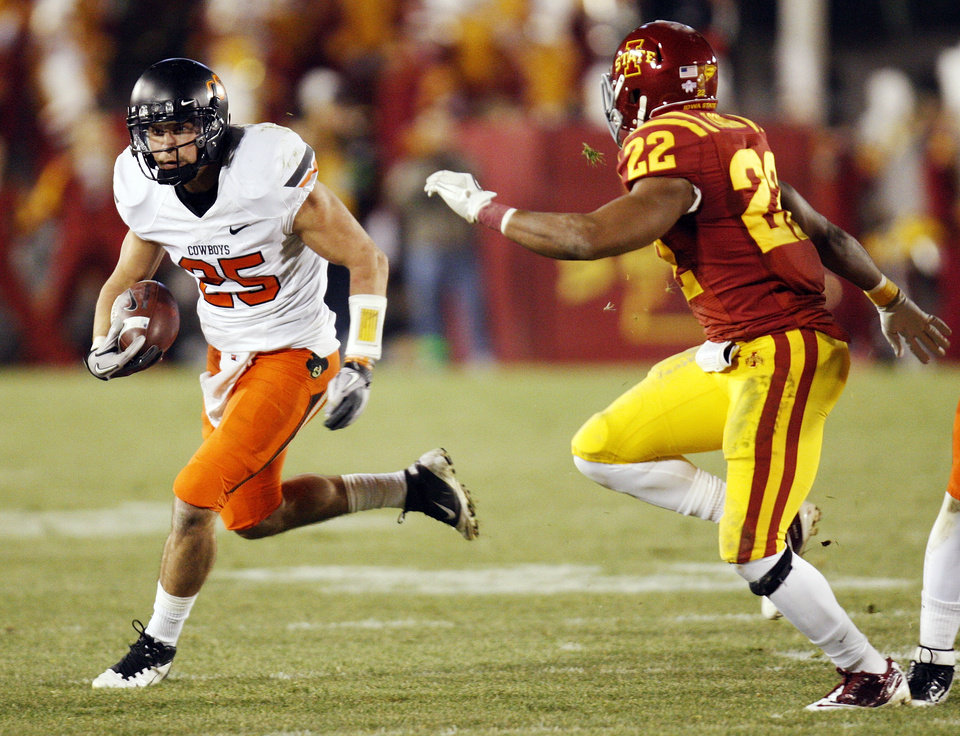 Photo - OSU's Josh Cooper (25) runs after a catch as Ter'Ran Benton (22) of ISU defends during a college football game between the Oklahoma State University Cowboys (OSU) and the Iowa State University Cyclones (ISU) at Jack Trice Stadium in Ames, Iowa, Friday, Nov. 18, 2011. Photo by Nate Billings, The Oklahoman