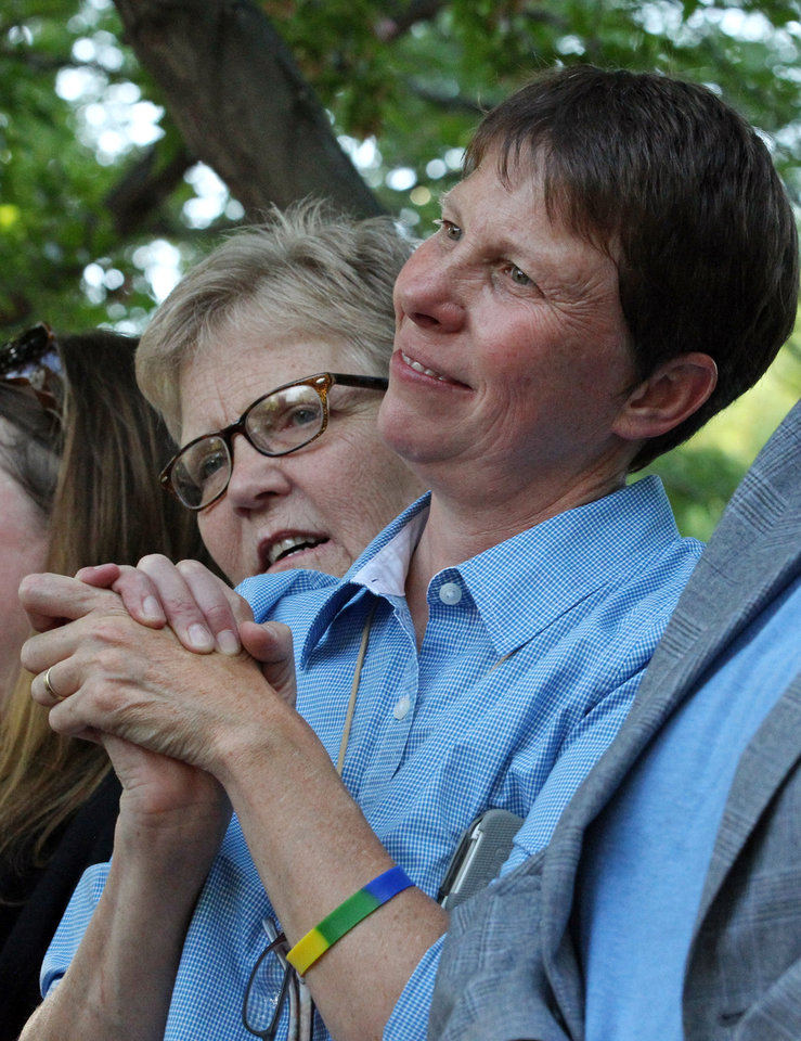 Photo - Laurie Wood, left, and spouse Kody Partridge gather with about 300 people in a downtown park to celebrate the gay marriage ruling Wednesday, June 25, 2014, in Salt Lake City. A federal appeals court on Wednesday ruled for the first time that states must allow gay couples to marry, finding the Constitution protects same-sex relationships and putting a remarkable legal winning streak across the country one step closer to the U.S. Supreme Court. (AP Photo/Rick Bowmer)
