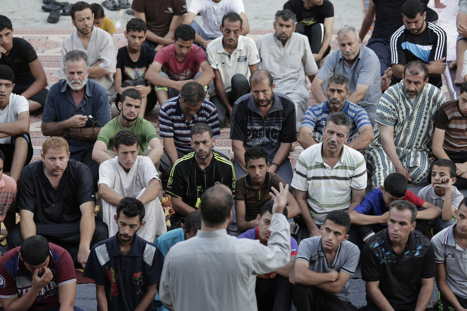 Photo - Palestinians listen to a sermon as they pray in the courtyard of a U.N. school in Gaza City, Monday, July 28, 2014. The school, one of dozens of emergency shelters for those who have fled the fighting. It's the morning of Eid al-Fitr, the three-day holiday that caps the Muslim fasting month of Ramadan. In normal times, the men would have worshipped at their neighborhood mosques. However, 20 mosques have been hit by Israeli warplanes so far, according to Palestinian officials. Israel says Hamas stores weapons and rockets in houses of worship. The men prefer to perform Eid prayers in the relative safety of the school. (AP Photo/Lefteris Pitarakis)