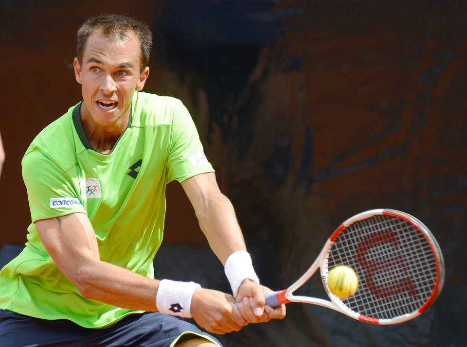Photo - Czech Republic's Lukas Rosol  returns  a ball to  Roberto Bautista Agut from Spain, during the final match of the Mercedes Cup ATP tennis tournament in Stuttgart, Germany, Sunday July 13, 2014.  (AP Photo/dpa, Daniel Maurer)