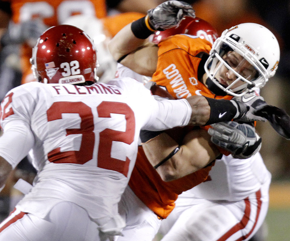 Photo - Oklahoma State's Bo Bowling (9) is brought down by Oklahoma's Jamell Fleming (32) during the Bedlam college football game between the University of Oklahoma Sooners (OU) and the Oklahoma State University Cowboys (OSU) at Boone Pickens Stadium in Stillwater, Okla., Saturday, Nov. 27, 2010. Photo by Chris Landsberger, The Oklahoman