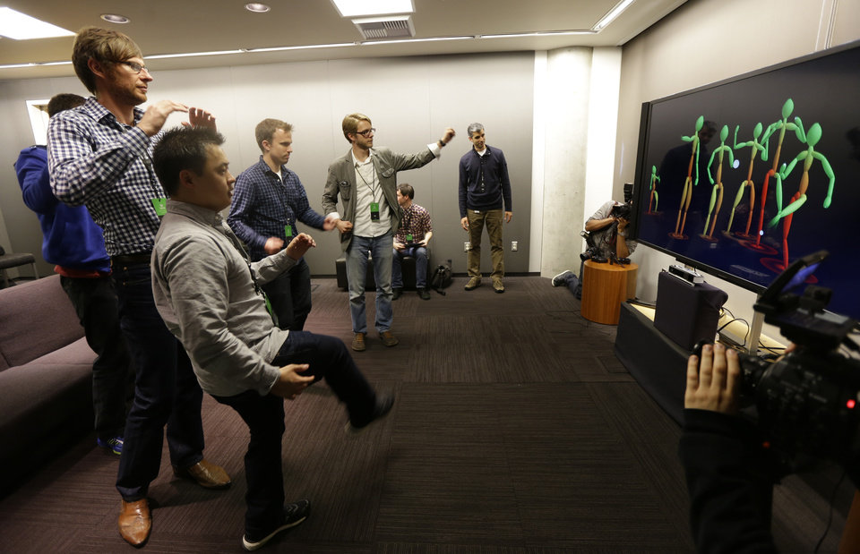 Photo - A group of visiting journalists try out the improved motion-detecting capabilities of the new Kinect controller for Microsoft's next-generation Xbox One entertainment and gaming console system, Tuesday, May 21, 2013, in Redmond, Wash. The new Kinect, which will come standard with the Xbox One can also see users in total darkness and has a wider field of view than the previous Kinect device in use with the Xbox 360. (AP Photo/Ted S. Warren)