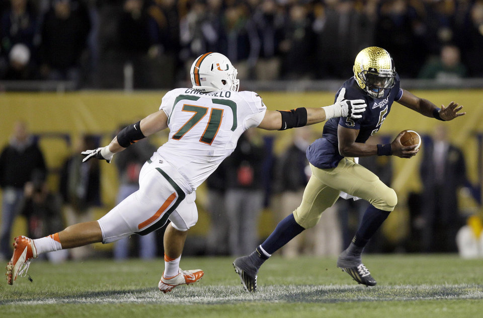 Notre Dame quarterback Everett Golson, right, eludes the grasp of Miami defensive lineman Anthony Chickillo during the first half of an NCAA college football game at Soldier Field Saturday, Oct. 6, 2012, in Chicago. (AP Photo/Nam Y. Huh)