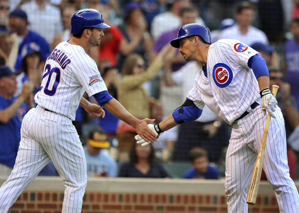 Photo - Chicago Cubs' Justin Ruggiano celebrates with John Baker after Ruggiano scored on a Ryan Sweeney single during the ninth inning of a baseball game against the Tampa Bay Rays in Chicago, Friday, Aug. 8, 2014. (AP Photo/Paul Beaty)