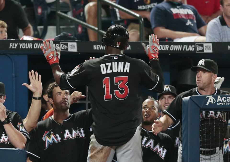 Photo - Miami Marlins center fielder Marcell Ozuna (13) celebrates with his teammates after scoring the game-winning run in the ninth inning of a baseball game against the Atlanta Braves, Thursday, July 24, 2014, in Atlanta. Miami won 3-2. (AP Photo)