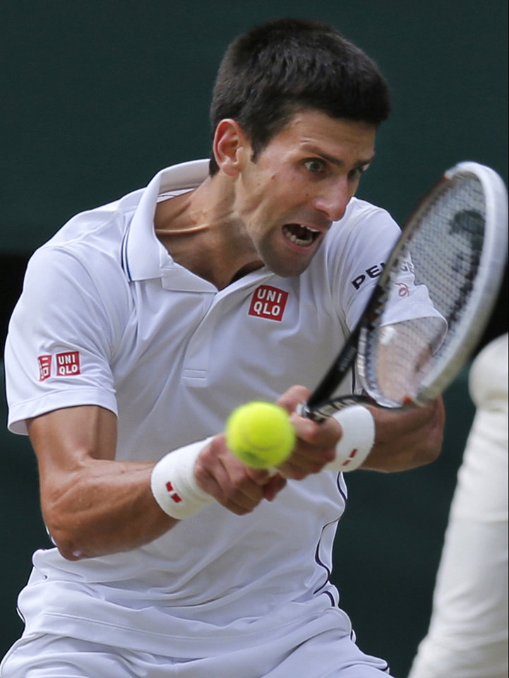 Photo - Novak Djokovic of Serbia plays a return to Roger Federer of Switzerland during the men's singles final at the All England Lawn Tennis Championships in Wimbledon, London, Sunday, July 6, 2014. (AP Photo/Pavel Golovkin)
