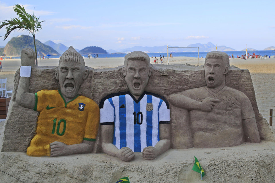 Photo - A sand sculpture featuring soccer players, from left to right, Neymar of Brazil, Lionel Messi of Argentina and Cristiano Ronaldo of Portugal, on Copacabana beach in Rio de Janeiro, Brazil, Monday, June 2, 2014. The 2014 Brazil World Cup is set to begin in a few days, with Brazil and Croatia competing in the opening match on June 12. (AP Photo/Hassan Ammar)