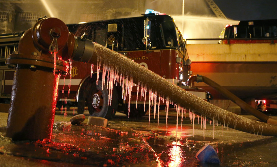 Icicles form on a fire hose from single digit temperatures as Chicago firefighters battle a five-alarm blaze in a warehouse on the city\'s South Side, Bridgeport neighborhood Wednesday, Jan. 23, 2013, in Chicago. (AP Photo/Charles Rex Arbogast)
