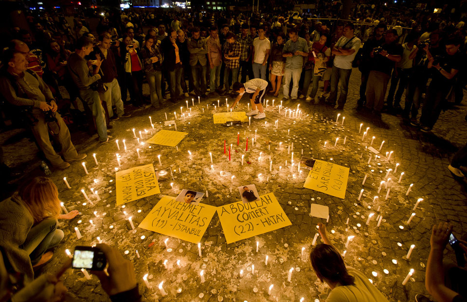 Photo - People light candles for the victims of the protests at Taksim square, in Istanbul, early Saturday, June 15, 2013. Protesters were holding debates in several locations in Gezi Park to discuss the results of a meeting their representatives had with the prime minister and whether his proposal was enough for them to end their occupation of the park. (AP Photo/Vadim Ghirda)