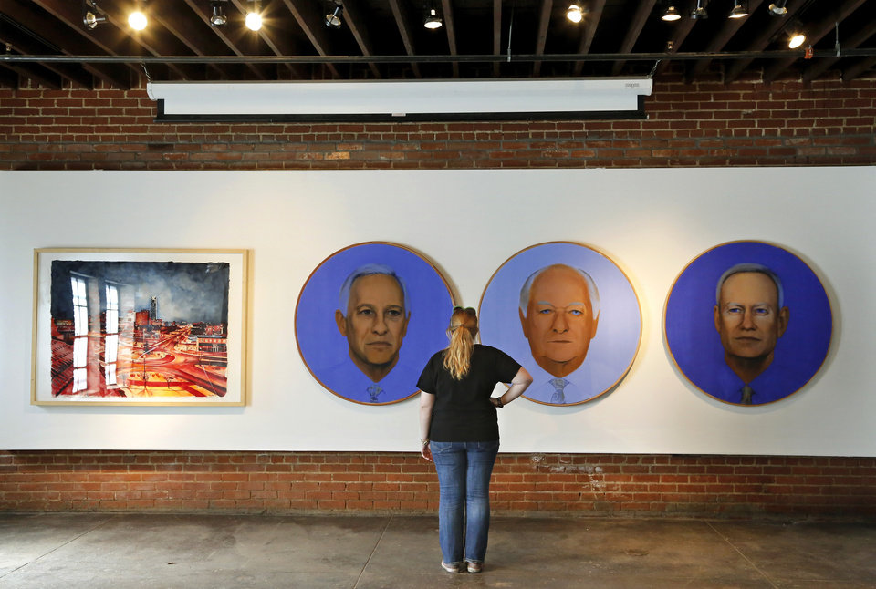 Photo -      Kendall Brown, executive director of Individual Artists of Oklahoma, looks at paintings of three Oklahoma City mayors painted by Richard McKown. An exhibit in honor of the 20th anniversary of MAPS is planned at the IAO Gallery on Film Row. Photo by Jim Beckel, The Oklahoman   Jim Beckel -
