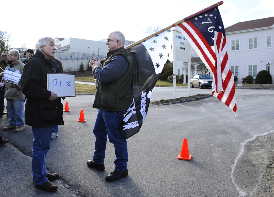 Photo - John Woodall. left, of Newtown, Conn.,  carries a sign that he says indicated the percentage of Americans who support universal background checks speaks with Gordon Jones of Southbury, Conn., a supporter of gun rights during a rally outside the National Shooting Sports Foundation headquarters  in Newtown  Thursday, March 28, 2013.  Search warrants released Thursday, March 28, 2013, revealed that an arsenal of weapons including guns, more than a thousand rounds of ammunition, a bayonet and several swords was seized at Adam Lanza's home.  Lanza killed his mother, Nancy Lanza in their home before he forced his way into Sandy Hook Elementary School in Newtown, Conn, killing 26 people.(AP Photo/Jessica Hill)