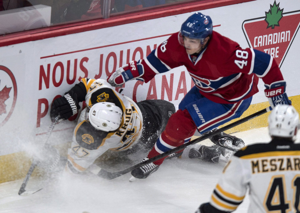 Photo - Boston Bruins' Torey Krug crashesinto the boards in front of Montreal Canadiens' Daniel Briere during first period NHL hockey action Wednesday, March 12, 2014 in Montreal. (AP Photo/The Canadian Press, Paul Chiasson)