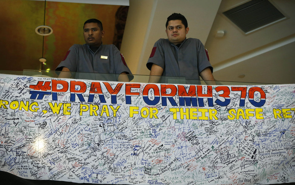 Photo - Hotel staff stand next to messages written to people involved with the missing Malaysia Airlines jetliner MH370 at a hotel in Putrajaya, Malaysia, Thursday, March 20, 2014. Four military search planes were dispatched Thursday to try to determine whether two large objects bobbing in a remote part of the Indian Ocean were part of a possible debris field of the missing Malaysia Airlines flight. (AP Photo/Vincent Thian)