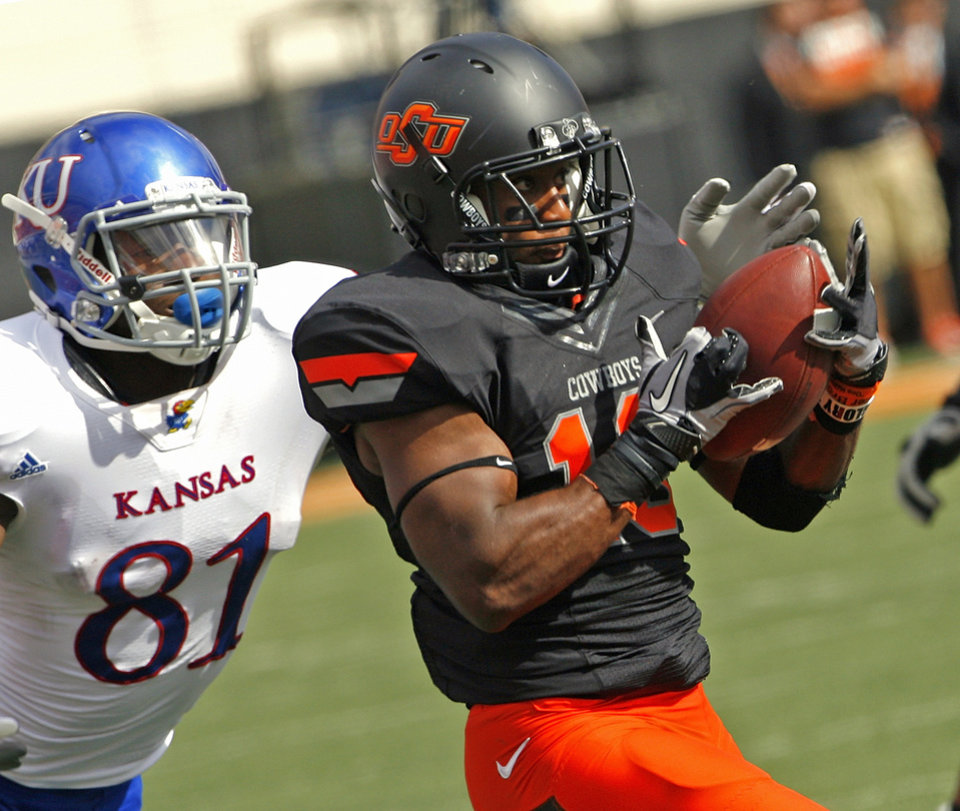 Photo - Oklahoma State's Brodrick Brown (19) intercepts a pass in front of Kansas' Marquis Jackson (81) during a college football game between the Oklahoma State University Cowboys (OSU) and the University of Kansas Jayhawks (KU) at Boone Pickens Stadium in Stillwater, Okla., Saturday, Oct. 8, 2011 Photo by Steve Sisney, The Oklahoman