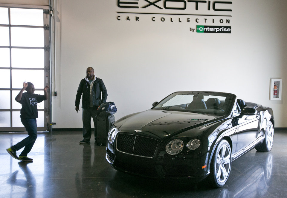 Photo - In this Wednesday, March, 26, 2014 photo, Herbert Igbanugo, middle, and his son,  from Minneapolis, Minn.,  look at a 2014 Bentley Continental GT displayed at the Enterprise Exotic Car Collection showroom near Los Angeles International Airport. (AP Photo/Damian Dovarganes)
