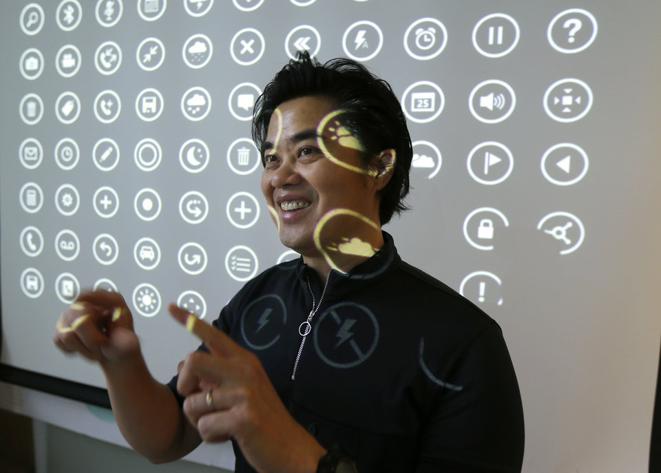 "Photo - In this photo taken July 3, 2014, Albert Shum, who heads interaction design across a range of Microsoft products including personal computer operating systems, Xbox game consoles, and phones, poses for a photo in front of a projection of icons used by those systems, in Redmond, Wash. A former designer for shoemaker Nike, Shum was part of the team that revolutionized the Windows Phone design to feature the boxy, so-called ""live tiles"" that are central to the touch-based interface in Windows 8. (AP Photo/Ted S. Warren)"