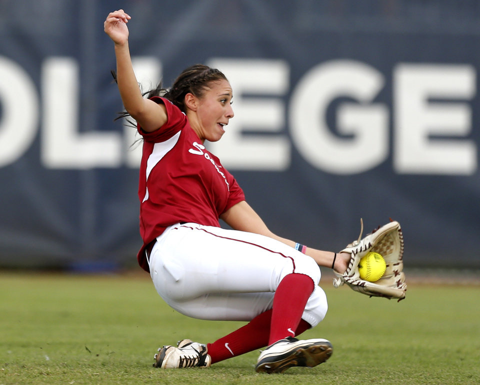 Oklahoma\'s Destinee Martinez (00) makes a sliding catch during Women\'s College World Series softball game at ASA Hall of Fame Stadium in Oklahoma City, Tuesday, June 4, 2013. Photo by Sarah Phipps, The Oklahoman
