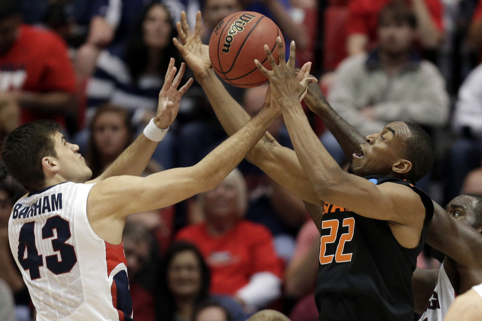 Photo - Oklahoma State guard Markel Brown, right, and Gonzaga forward Drew Barham battle for a loose ball during the first half in a second-round game in the NCAA college basketball tournament Friday, March 21, 2014, in San Diego. (AP Photo/Gregory Bull)