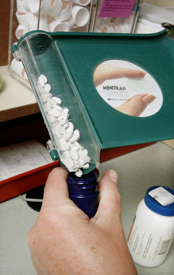 Pills are poured into a bottle after being counted at Sherry's Discount Pharmacy in Edmond.  PHOTO ILLUSTRATION BY PAUL B. SOUTHERLAND, THE OKLAHOMAN