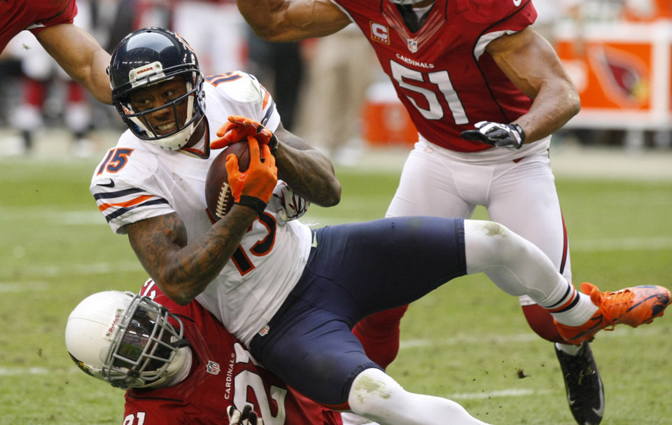 Photo - Chicago Bears wide receiver Brandon Marshall (15) is tackled by Arizona Cardinals cornerback Patrick Peterson (21) during the first half of an NFL football game, Sunday, Dec. 23, 2012, in Glendale, Ariz. (AP Photo/Rick Scuteri)
