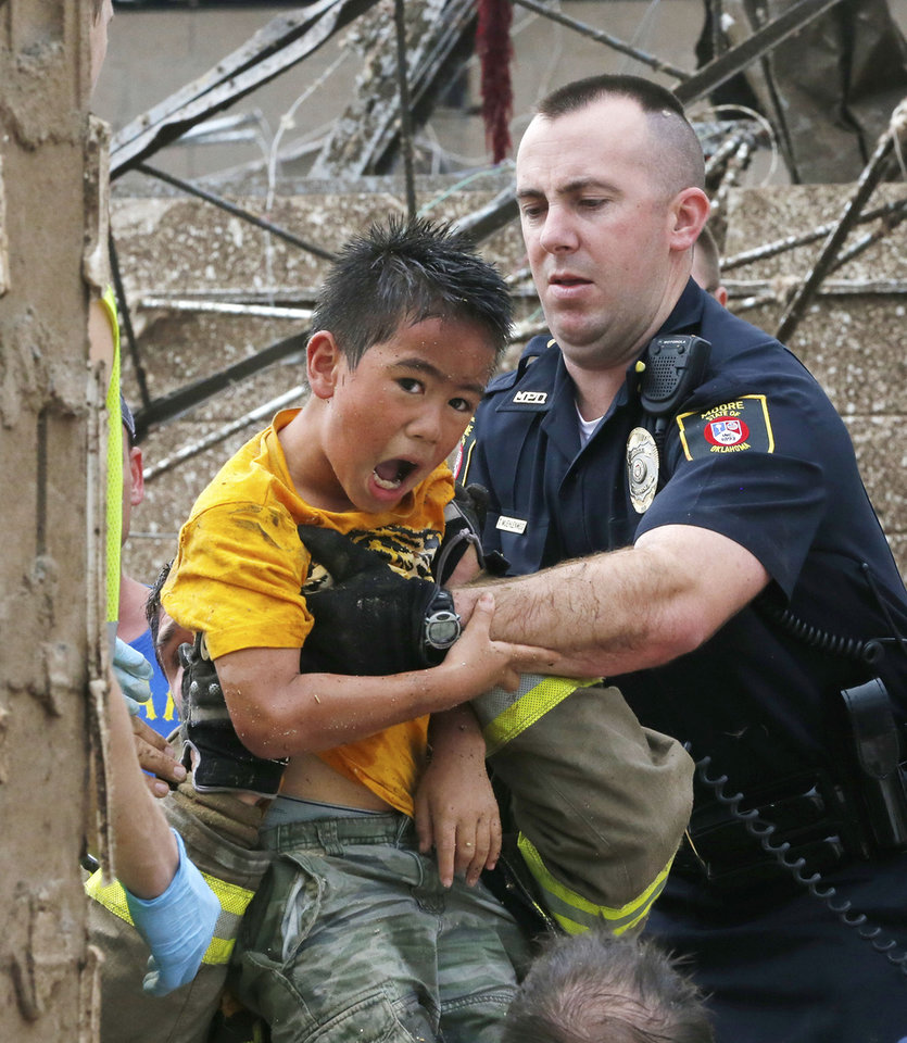 Photo - A boy is pulled from beneath a collapsed wall at the Plaza Towers Elementary School following a tornado in Moore, Okla., Monday, May 20, 2013. A tornado as much as a mile (1.6 kilometer) wide with winds up to 200 mph (320 kph) roared through the Oklahoma City suburbs Monday, flattening entire neighborhoods, setting buildings on fire and landing a direct blow on the elementary school. (AP Photo Sue Ogrocki)