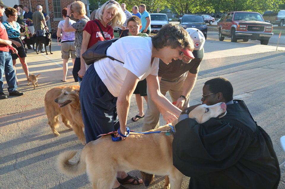 The Rev. Gerard Nsabimana, University of Central Oklahoma Wesley Foundation minister, hugs Lucky, a dog owned and held by Judy Elliot,  during the blessing of the animals at Edmond's First United Methodist Church. Photo by Ben Bigler, The Oklahoman <strong>Ben Bigler - The Oklahoman</strong>