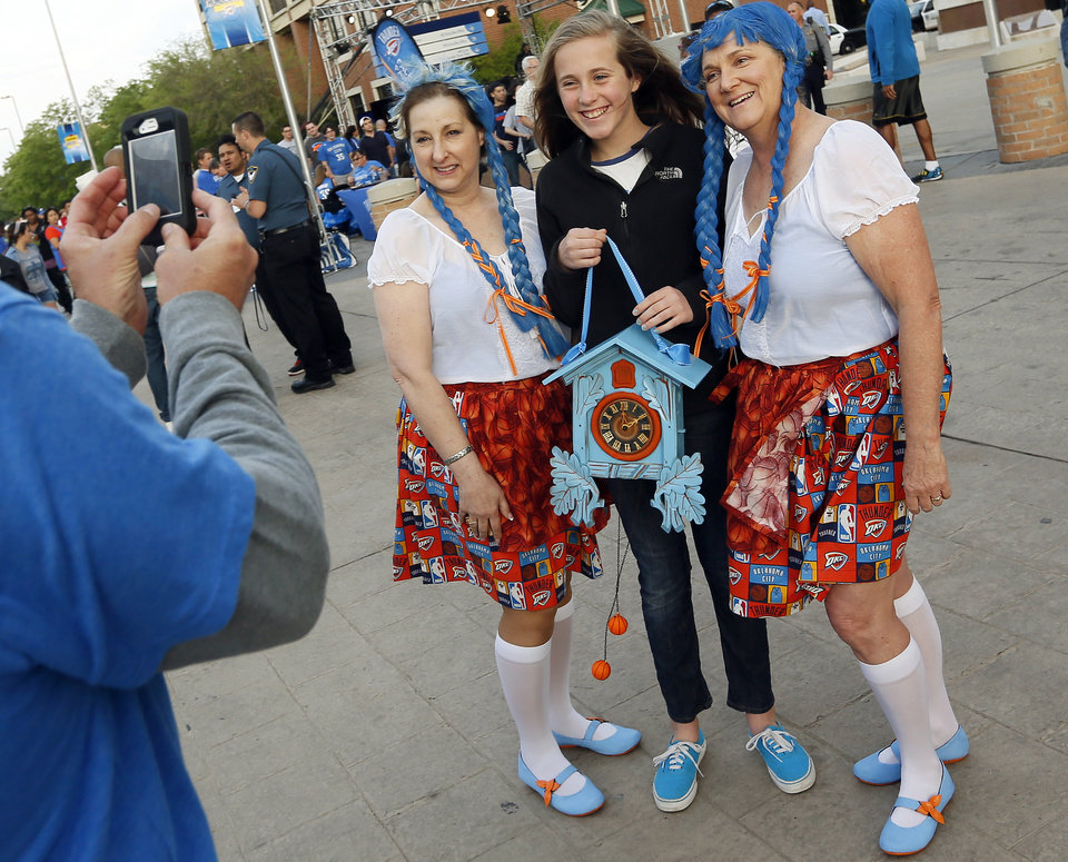 Photo - Kent Walstad takes a picture of his daughter, Sydney Walstad, middle, with Vanessa Shadix, left, and Cheri Rich, right, who are dressed in Thunder-themed Swiss costumes before Game 5 in the first round of the NBA playoffs between the Oklahoma City Thunder and the Houston Rockets at Chesapeake Energy Arena in Oklahoma City, Wednesday, May 1, 2013. The women wore the costumes to root for Swiss Thunder player Thabo Sefolosha.  Photo by Nate Billings, The Oklahoman