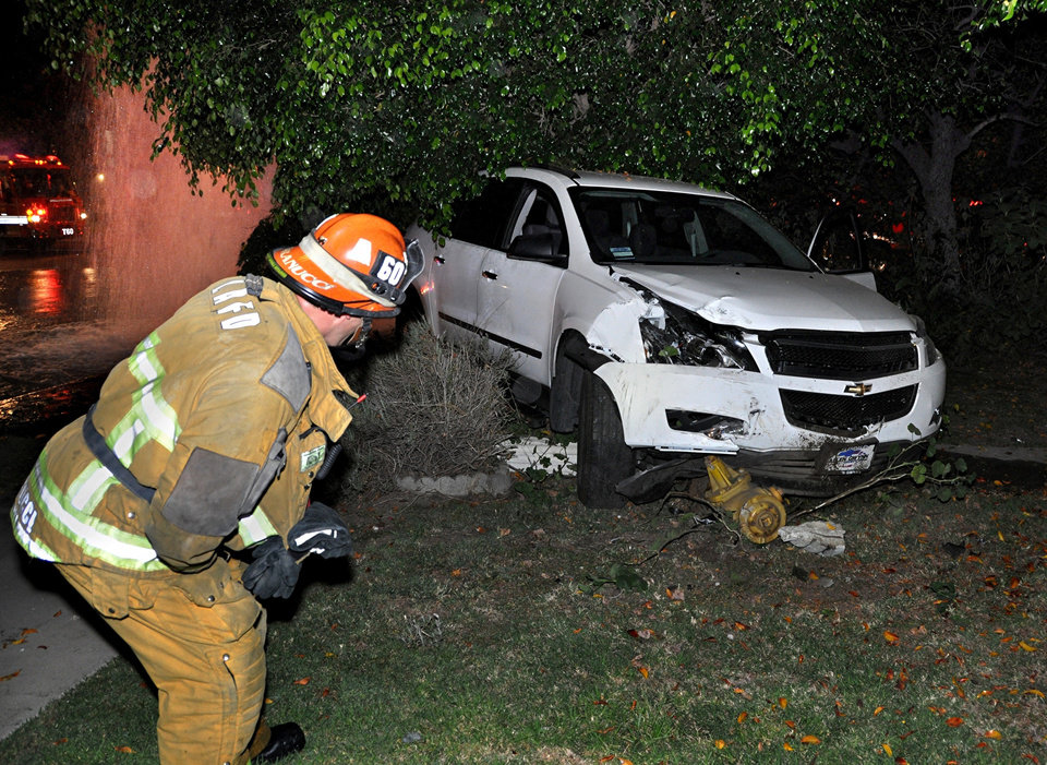 FILE - In this Aug. 22, 2012 file photo, Los Angeles fire captain Cristian Granucci examines the wreckage of an SUV that knocked over a fire hydrant and power pole, as water from the hydrant gushes in the background, after a collision in the North Hollywood section of Los Angeles. Seven people suffered electric shocks, including two women who were electrocuted, as they rushed to the scene help and were water from the hydrant was electrified by live wires on the utility pole. The driver, Aman Samsonian, has been ordered to stand trial for vehicular manslaughter in the electrocution deaths. (AP Photo/Rick McClure, File)