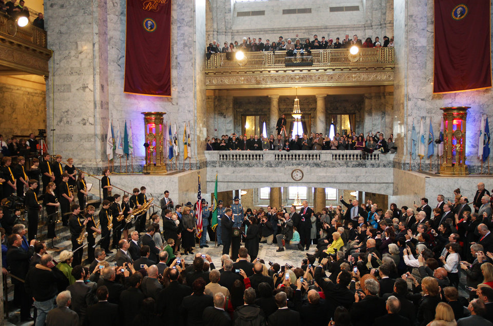 Jay Inslee, center left, is sworn in as Washington state Governor, Wednesday, Jan. 16, 2013, by Washington Supreme Court Chief Justice Barbara Madsen, center right, in the rotunda of the Legislative Building at the Capitol in Olympia, Wash. (AP Photo/Ted S. Warren)