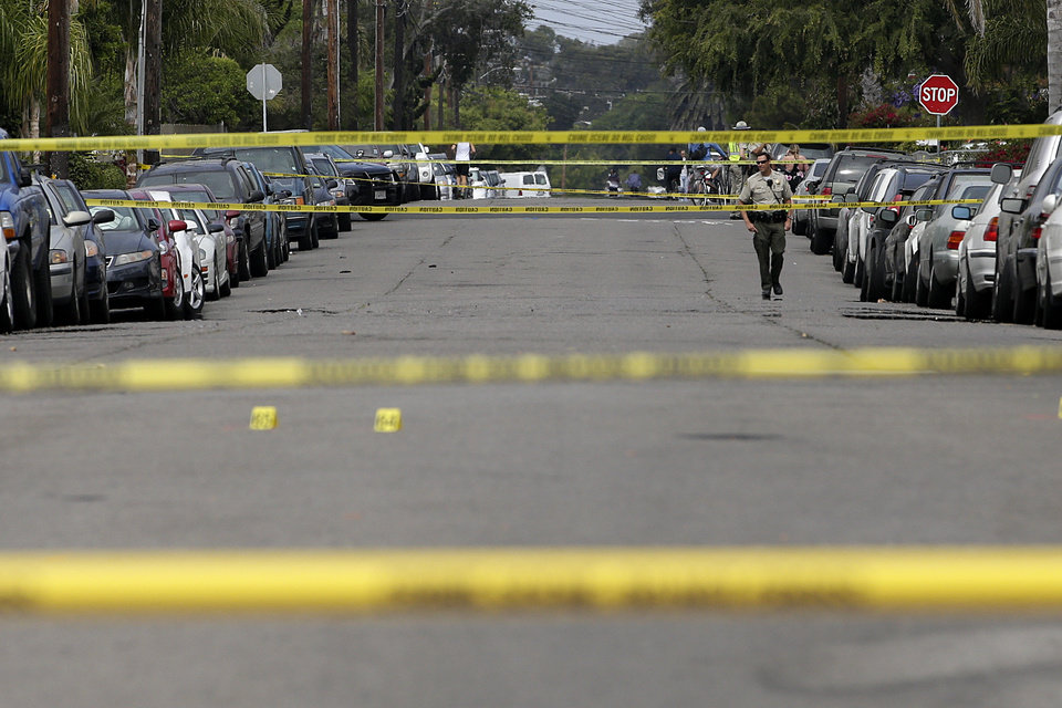 Photo - A Santa Barbara County deputy sheriff walks along the street near the scene of a shooting on Saturday, May 24, 2014, in Isla Vista, Calif. A drive-by shooter went on a rampage near a Santa Barbara university campus that left seven people dead, including the attacker, and others wounded, authorities said Saturday. (AP Photo/Jae C. Hong)