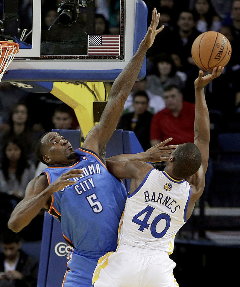 Photo - Oklahoma City Thunder's Kendrick Perkins, left, defends against Golden State Warriors' Harrison Barnes (40) during the first half of an NBA basketball game Wednesday, Jan. 23, 2013, in Oakland, Calif. (AP Photo/Ben Margot)