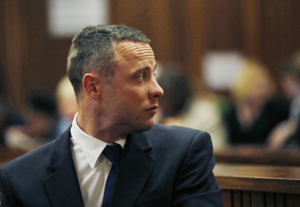 Photo - Oscar Pistorius looks back in a courtroom at the high court in Pretoria, South Africa, Tuesday, May 6, 2014. A man who lives next to the house where Pistorius fatally shot his girlfriend has testified at the athlete's murder trial about the night of the killing, saying he heard a man crying loudly and that he called the security of the housing estate for help. (AP Photo/Mike Hutchings, Pool)