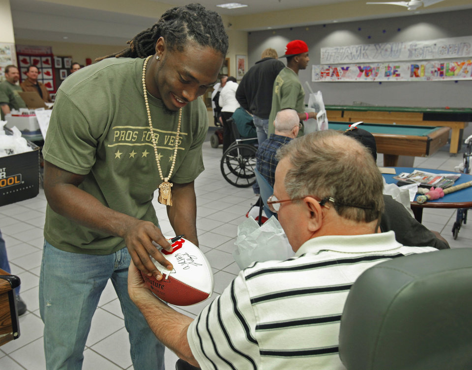 Photo -  University of Oklahoma football Quinton Carter autographs a football for Tom Swyear during a visit to the Veteran's Center by Carter's SOUL Foundation on Thursday, December 16, 2010, in Norman, Okla.   Photo by Steve Sisney, The Oklahoman