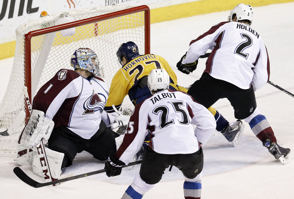 Photo - Nashville Predators forward Patric Hornqvist (27), of Sweden, falls into Colorado Avalanche goalie Semyon Varlamov (1), of Russia, as Hornqvist scores a goal in the second period of an NHL hockey game, Saturday, Jan. 18, 2014, in Nashville, Tenn. Also defending for the Avalanche are Maxime Talbot (25) and Nick Holden (2). (AP Photo/Mark Humphrey)