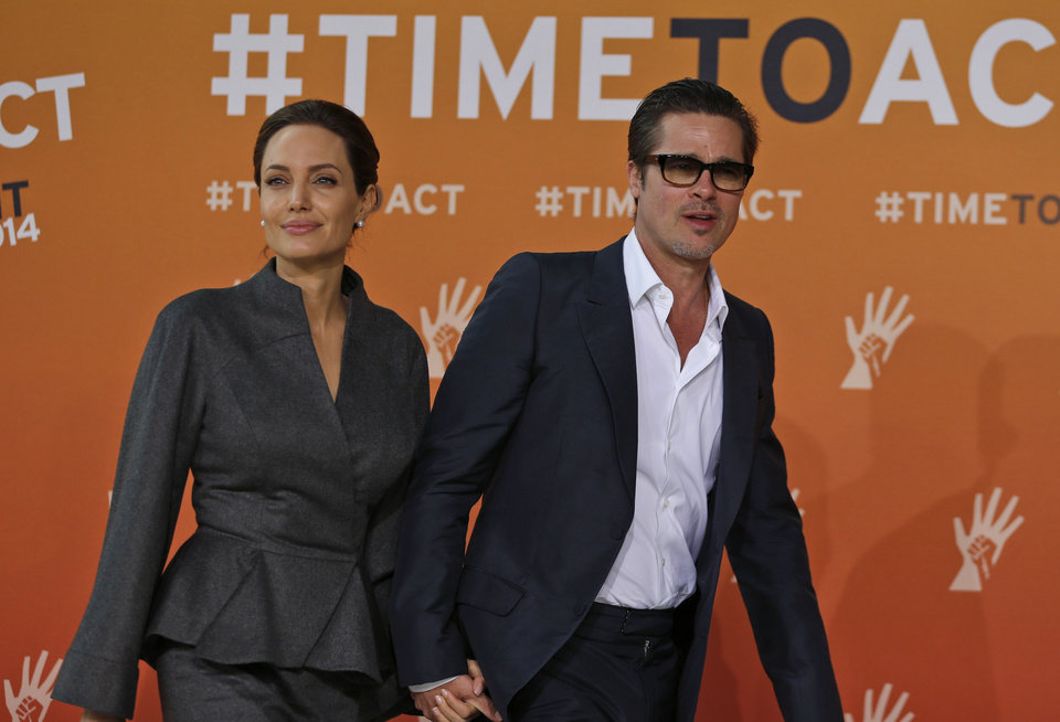 Photo - Angelina Jolie, left, special envoy of the United Nations High Commissioner for Refugees, and her partner Brad Pitt arrive at the 'End Sexual Violence in Conflict' summit in London, Friday, June 13, 2014. The Summit welcomes governments from over 100 countries, over 900 experts, NGOs, Faith leaders, and representatives from international organizations across the world. (AP Photo/Lefteris Pitarakis)